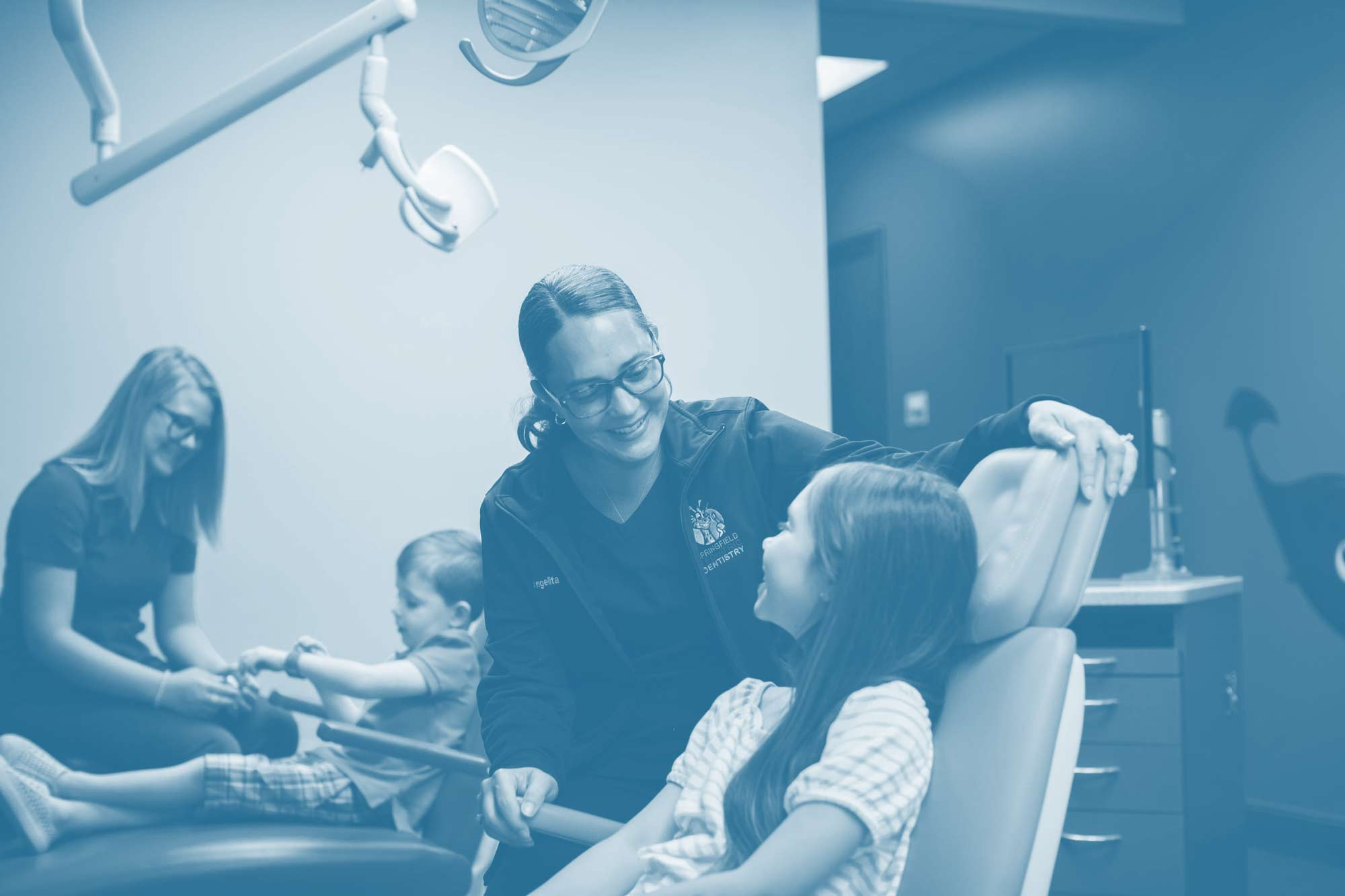 Photo of a pediatric dentist, a patient sitting in a dental chair, and a team member