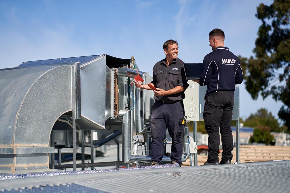 HVAC technicians inspect air conditioning unit on roof, Ascott Primary School, South Australia