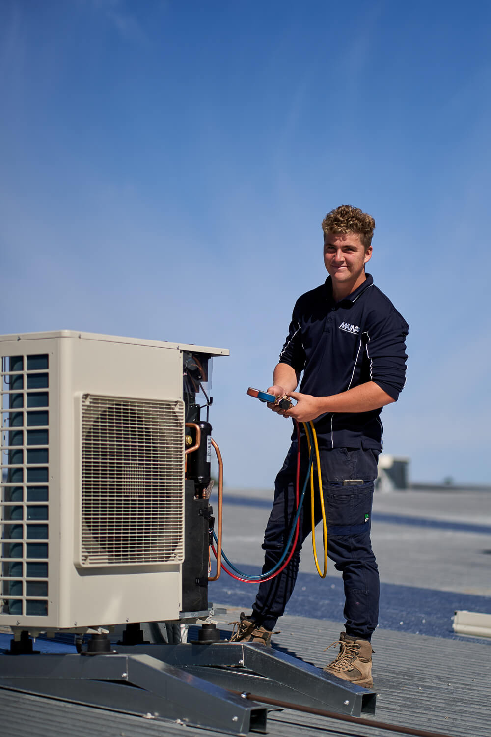 HVAC technician inspects air conditioning unit, Adelaide South Australia