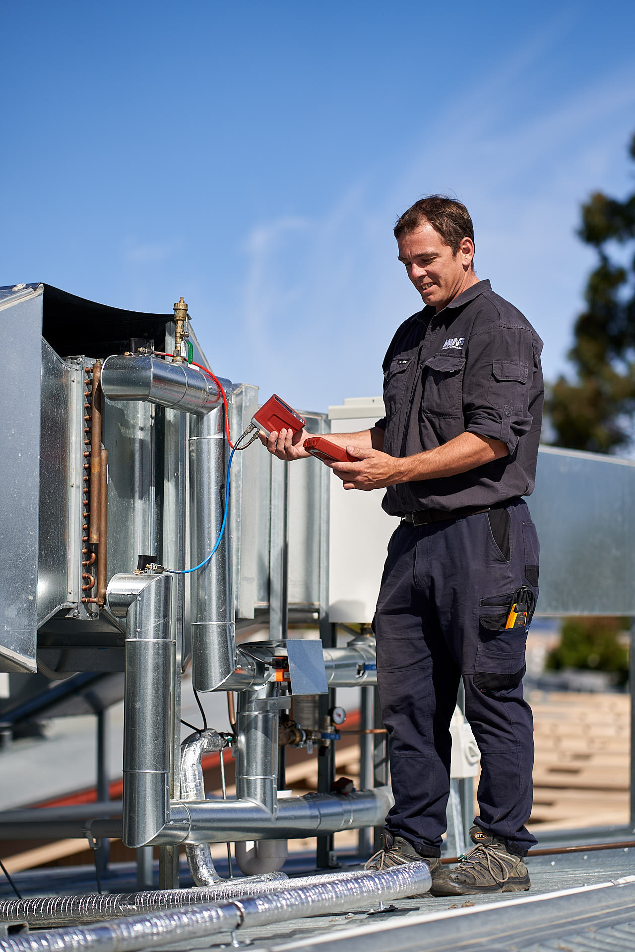 Commercial HVAC technician repairs unit in Adelaide