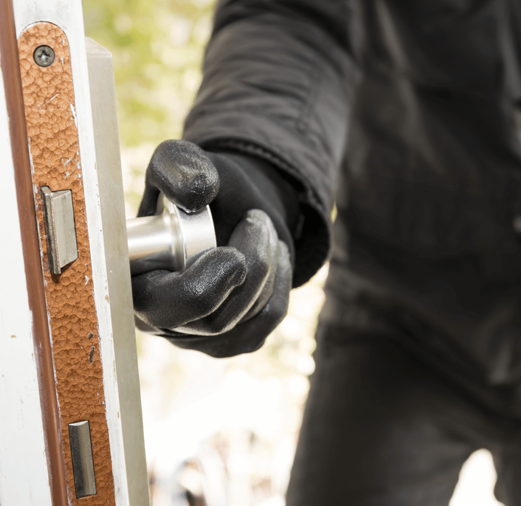 Image shows a hand wearing a black leather glove opening a door - Learn six myths about home protection
