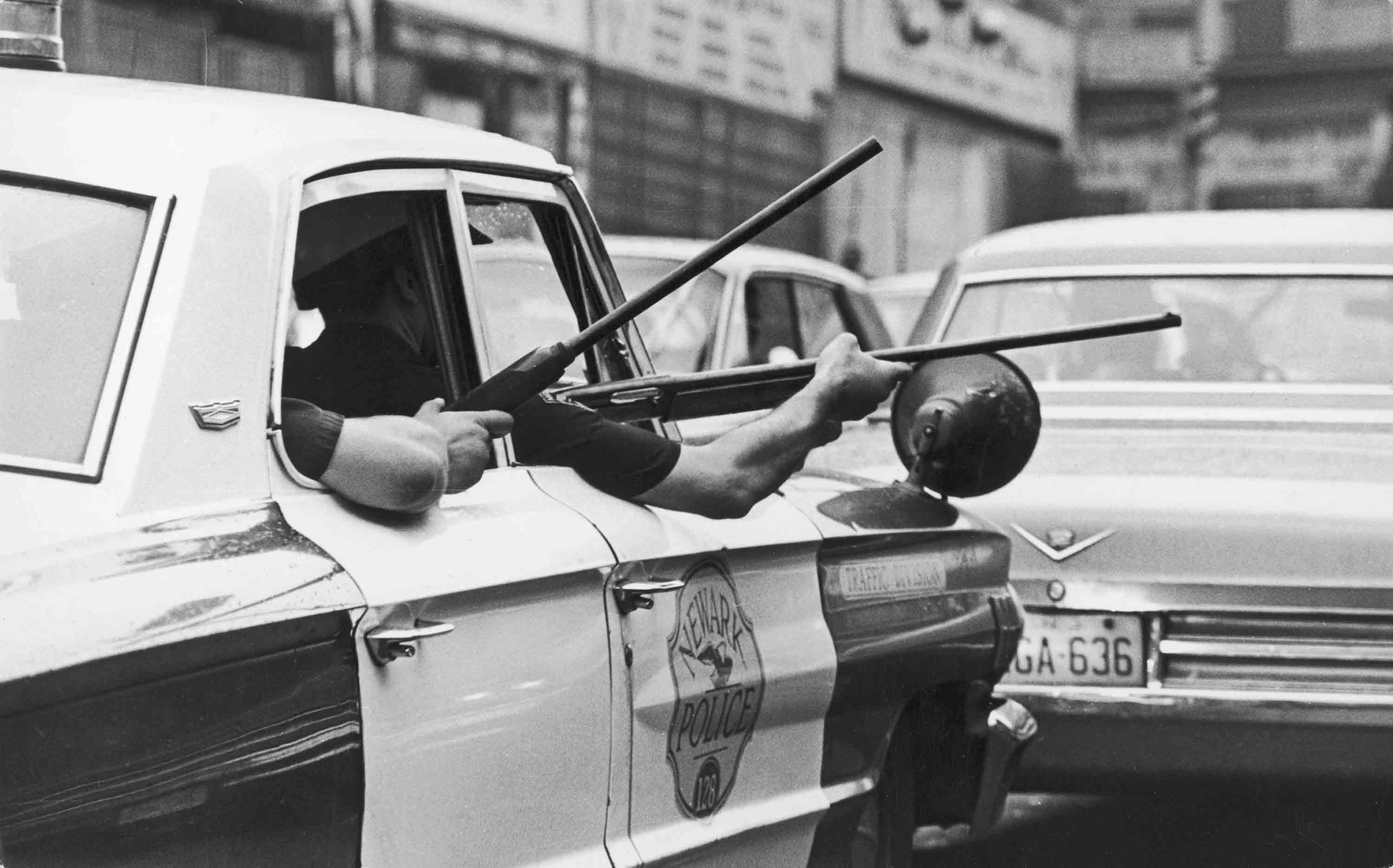 Police hold rifles out of the windows of a police cruiser during the Newark riots, Newark, July 14, 1967