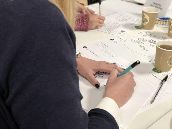 A Design Hop participant writing