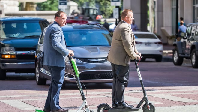 Lime and Bird scooter riders travel along downtown Indianapolis streets on Thursday, June 28, 2018.