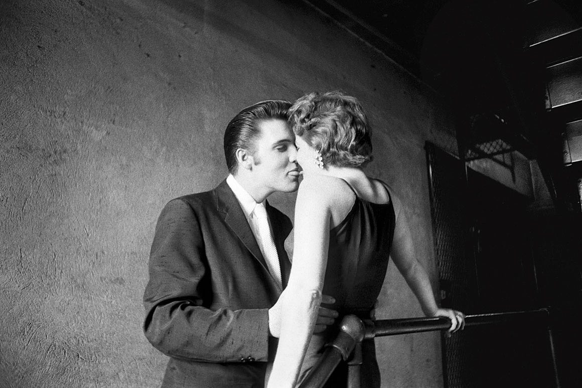 "Happy Valentine's Day!   Named the sexiest photo of all time by actress Diane Keaton, ""The Kiss"" was taken minutes before Elvis' concert at The Mosque Theater in 1956.   From a 2014 @smithsonianmagazine interview with photographer Alfred Wertheimer on how he captured ""The Kiss"":   ""I was in the men's room on the floor above the stage area at the Mosque Theater in Richmond, Virginia, on June 30 of 1956. I got more or less sidetracked and then I turned around and said: ""Where's Elvis?"" Elvis had disappeared. I go down the stairs of the theater. I get down to the landing where the stage area is. You've now got 3,000 kids, mostly girls, in there, and the ""Elvis Presley Show"" is going on; except there's no Elvis Presley around. I look down this long, narrow passageway, the light at the end of the tunnel. There's a silhouette of two people at the far end, and I say, ""Oh yes, there's Elvis, with a girl, his date for the day."" Do I interrupt them? Do I squeeze off a frame or two from a distance or do I go closer in? Well, you start off becoming a human tripod, because you don't want to start using flash. It's really quite dark.  ...  So now I'm not satisfied, typically. I'm not satisfied with what? I'm not satisfied with back lighting. I want front lighting. But the only way to get front lighting is to go beyond where they are. So I put on my best maintenance man voice and say, ""Excuse me, coming through."" I squeeze past the two of them. Again they don't pay attention to me because they're like hypnotizing each other.  I'm now set on the landing facing the two of them, and I'm setting myself with the frame. It's a fairly decent composition, and I'm waiting for something to happen within my frame. She says to him: ""Elvis, I'll betcha can't kiss me,"" and she sticks out her tongue just a teeny bit. And he says, ""I'll betcha I can,"" in a very masculine, cool way. And he then approaches the kiss, he's got his tongue stuck out just a wee bit, and he overshoots the mark.""  📷©️Alfred Wertheimer/MUUS Collection"