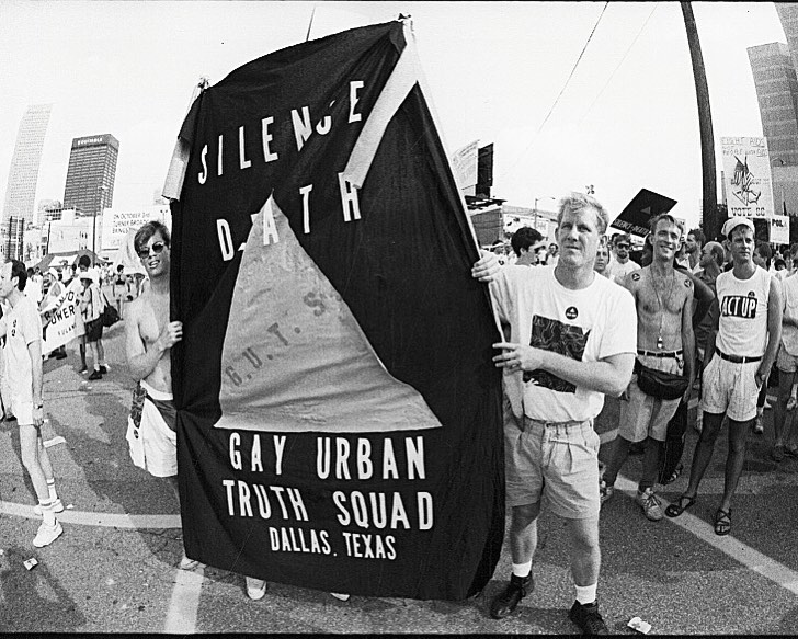 """Members of the Gay Urban Truth Squad (GUTS) with a 'Silence Equals Death' banner demonstrate outside the Omni Hotel during the Democratic National Convention in Atlanta, Georgia, July 17, 1988.  An excerpt on GUTS from the November 1996 Issue of D Magazine, article titled """"The Pink Mafia"""", by Kimberly Goad: """"The Gay Urban Truth Squad, led by activists William Waybourn, Bill Hunt, Bill Nelson and John Thomas, decided early on to adapt to Dallas' longtime aversion to confrontation while still using action to make a point. When GUTS staged a protest, streets were never blocked, no one was arrested. A GUTS protest was more like a cleverly orchestrated, photo-worthy street drama. In 1988, for instance, the bottom had already fallen out of the Dallas real estate market. [An] empty lot ... had been cleared for development only to have the developer ... file for bankruptcy. Declaring the empty lot a safety hazard, the city council voted to spend $500,000 to fill the giant hole the same year it voted to allot $55,000 to AIDS funding. Thirty-five members of GUTS arrived on the scene after the hole was tilled and turned it into a potter's field, hammering into the ground hundreds of white crosses bearing the names of people in Dallas County who had died of AIDS. Before GUTS left, the group erected a three-part sign: """"The City of Dallas Spent $500,000 Filling This Hole/The City of Dallas Spent $55,000 on AIDS/Dallas County AIDS Deaths Equals 793."""" The """"protest"""" was carried on the evening news. The following year, AIDS funding increased to $552,000.""""  © Fred W. McDarrah/MUUS Collection"""