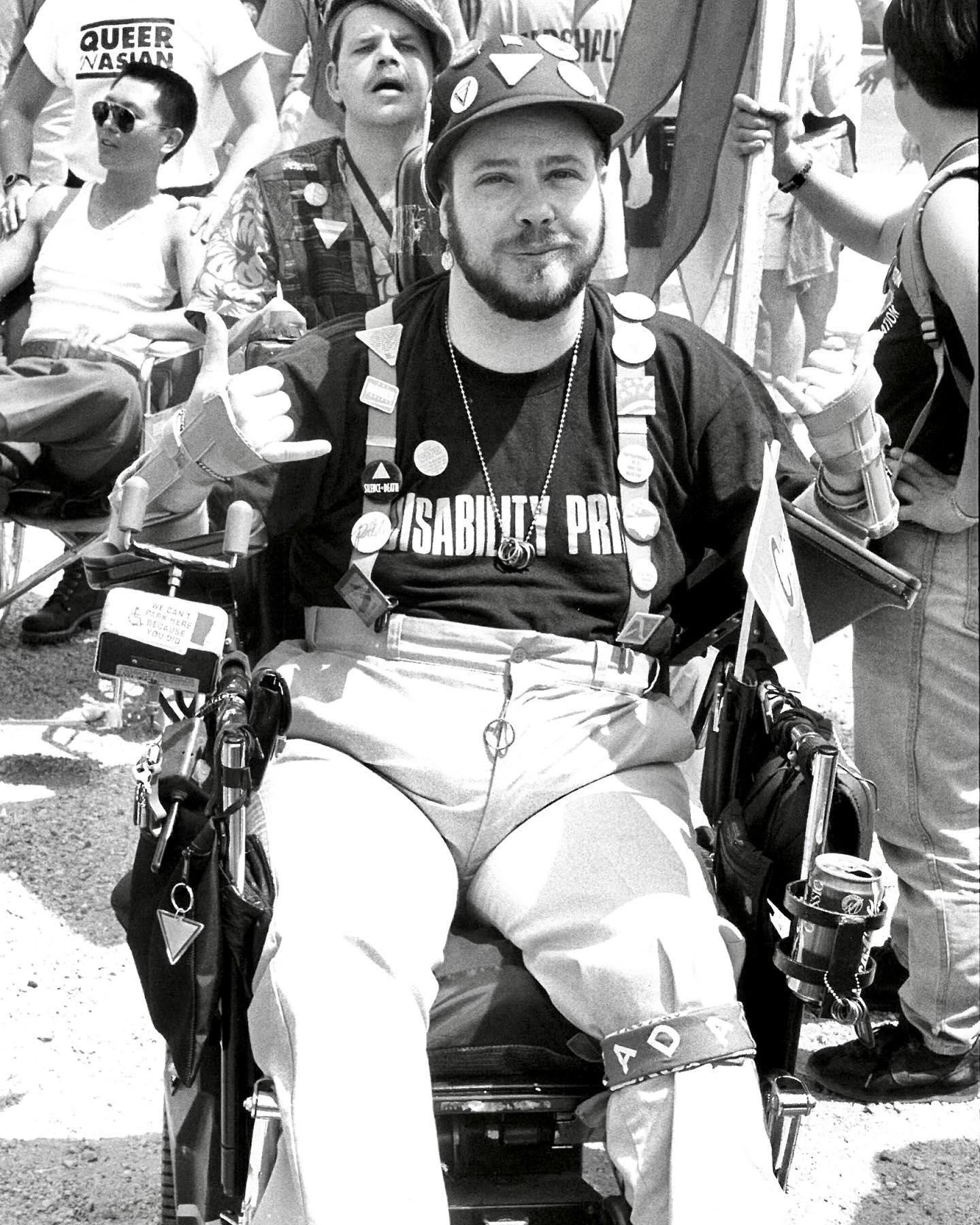 #OnThisDay in 2020, Erik von Schmetterling of @realnatlADAPT (Americans Disabled for Accessible Public Transportation), passed away at age 67. He is seen here at the 1993 March on Washington for Gay, Lesbian, and Bi Equal Rights and Liberation, in a shirt reading 'Disability Pride'.  Dr. Von Schmetterling was an out and proud disabled transman, born in Munich. The son of a Holocaust survivor who suffered severe PTSD, he was abandoned at age 3 and adopted by a family that then moved to the US. In a tribute written by his husband, Dr. von Schmetterling is described as turning to books and education as a refuge from trauma. He attended Queen's College in England on scholarship to study medicine, and after graduation, began a residency at Cleveland Metro Hospital.  However, his residency was cut short by a pulmonary embolism that caused him to start losing feeling in his limbs. He became unable to practice medicine and spent time in a home for the disabled and elderly - but after witnessing the mistreatment of folks in that home, felt called to Disability Rights. Erik moved into a wheelchair accessible apartment and started volunteering; he was the 1992-1994 President of Disabled In Action, and worked with ADAPT from 1988 to the time of his passing. He was a deeply compassionate person who believed that people with disabilities had the right to full inclusion and access to life.  Erik married James V. Shrode in a religious ceremony during an ADAPT protest. The two considered their participation in the March on Washington to be a particularly proud moment. They arranged accessibility and resources for disabled LGBTQ folks to attend, providing supportive community for attendees who, like Erik, faced the multiple hurdles of being gay, trans, and disabled. Erik and Jimmi helped make it possible for them to gather and visibly advocate for themselves as part of the larger LGBTQ community.    In honor of Erik and his belief in the power of education, Disability Pride PA  has f