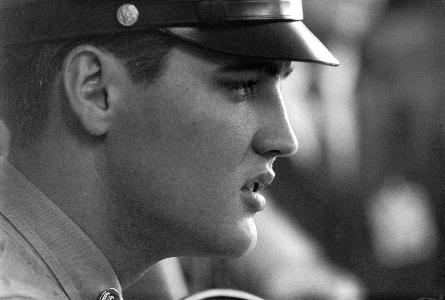 Elvis Presley left for his tour in the military #OnThisDay in 1958, when he shipped out to Germany alongside his fellow recruits. Crowds of people and press arrived to see him off from the Brooklyn Army Terminal in New York.  Image description: In image 1, Elvis is seen in profile at a press conference, in uniform. In image 2, he is seen again in uniform at his press conference. He holds a microphone to his chest and looks over his shoulder while a crowd of reporters is seen across the desk where he sits. In image 3, uniformed Elvis is ushered through a thick crowd of people. In image 4, Elvis is seen aboard the USS General George M. Randall. His fellow recruits are to his left and the last of his fans seeing him off reach out to him from his right.  © Alfred Wertheimer/MUUS Collection
