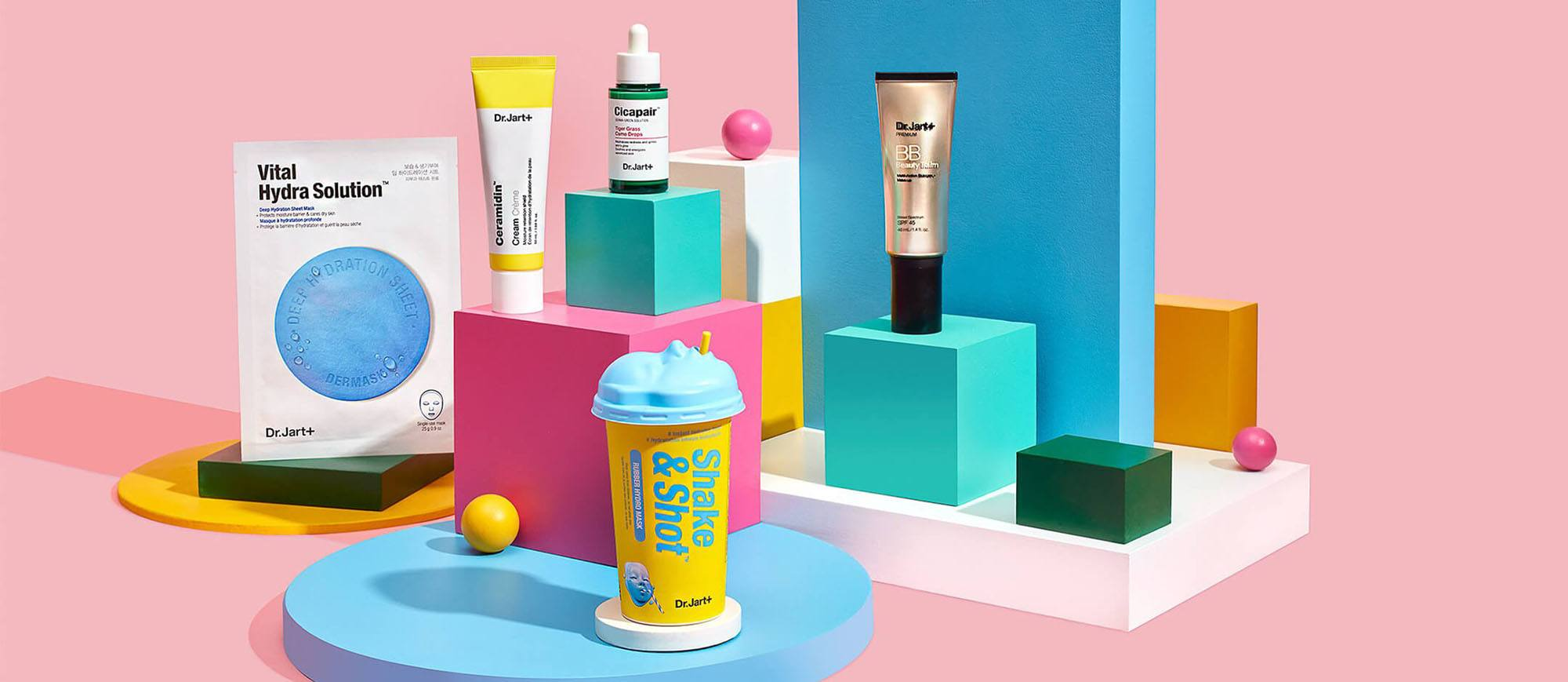 Different Dr. Jart products on various size pedestals on a pink background
