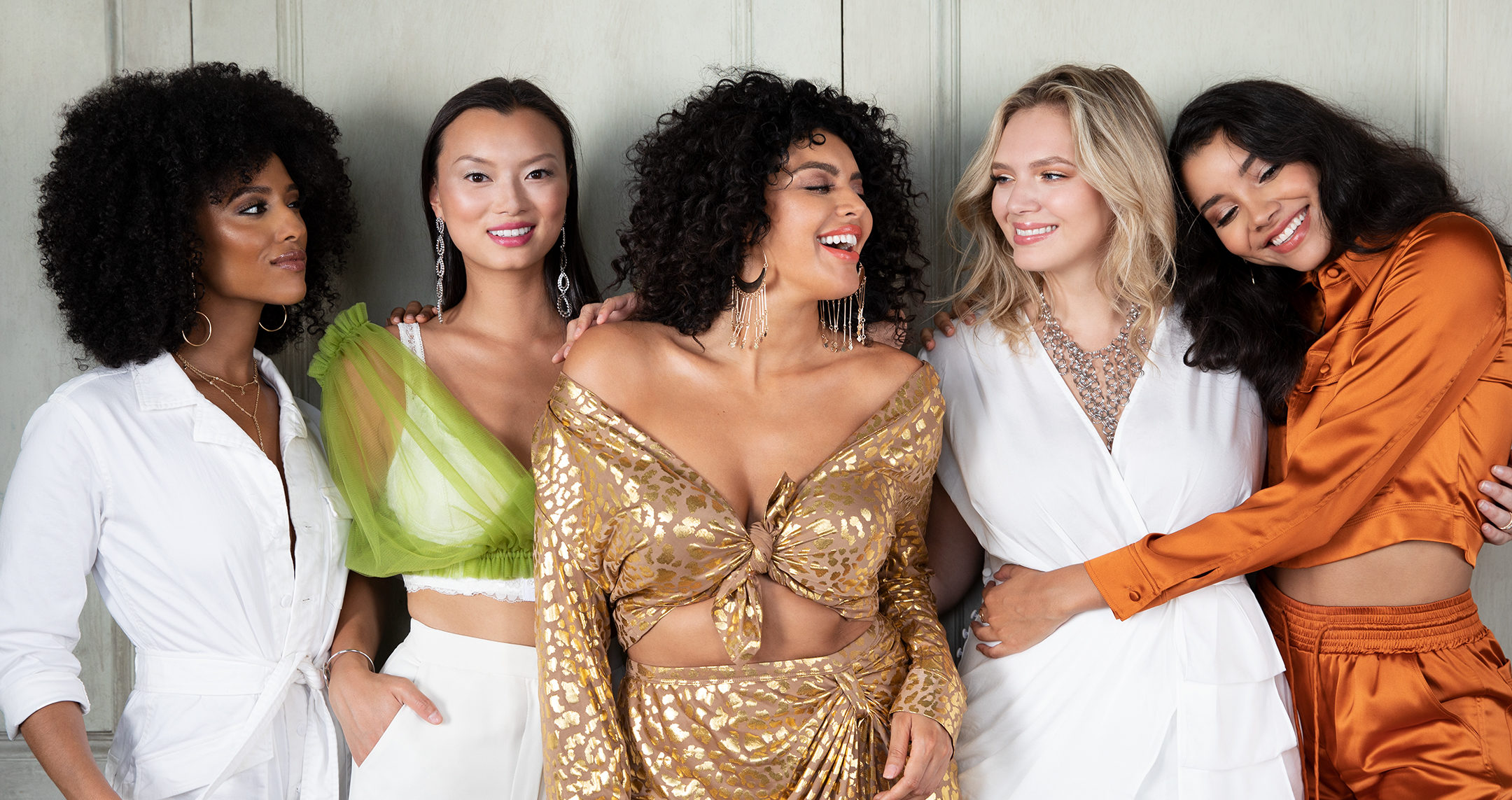 5 woman in choosy dresses smiling