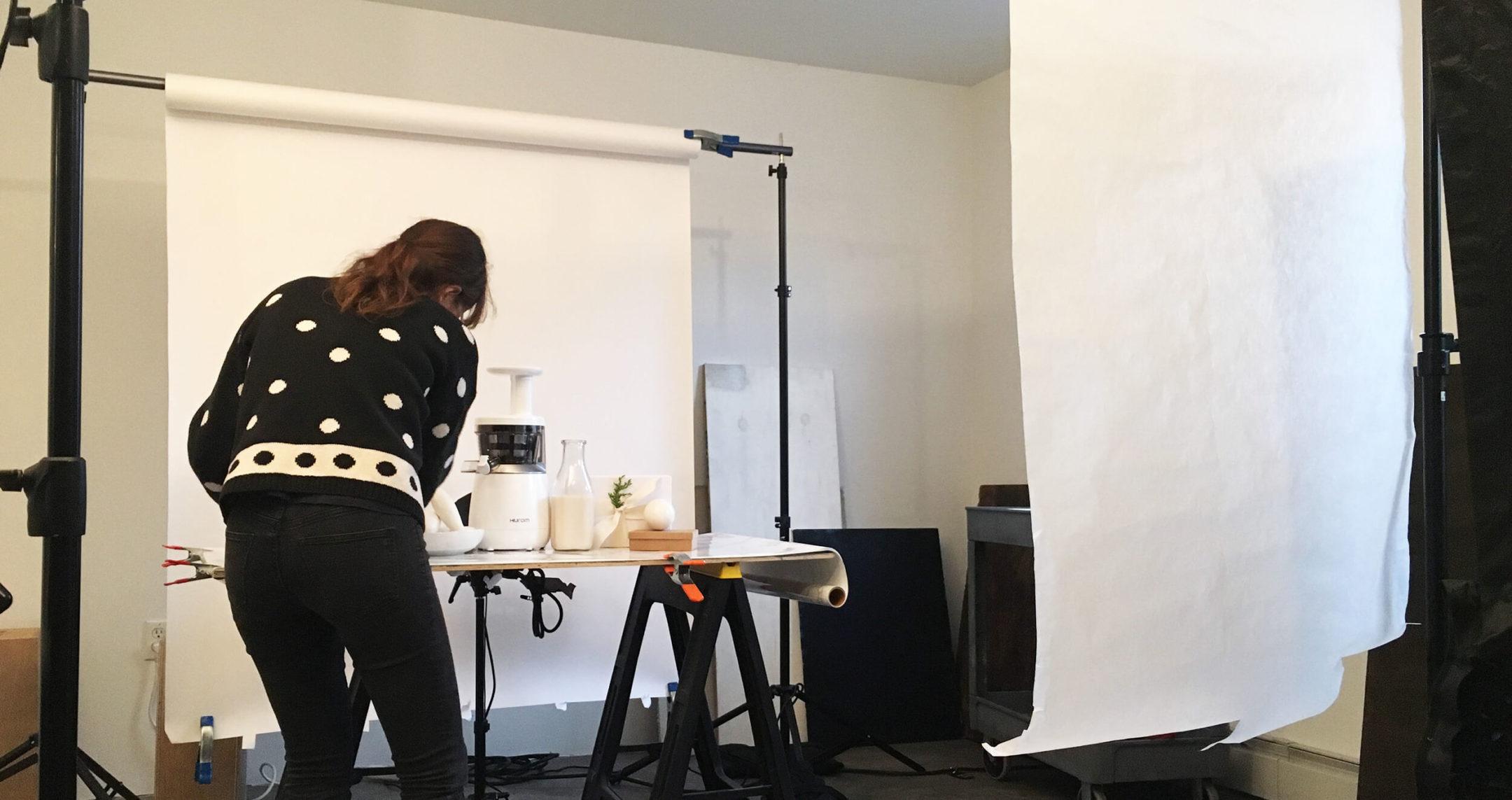 woman setting up photoshoot on white backdrop