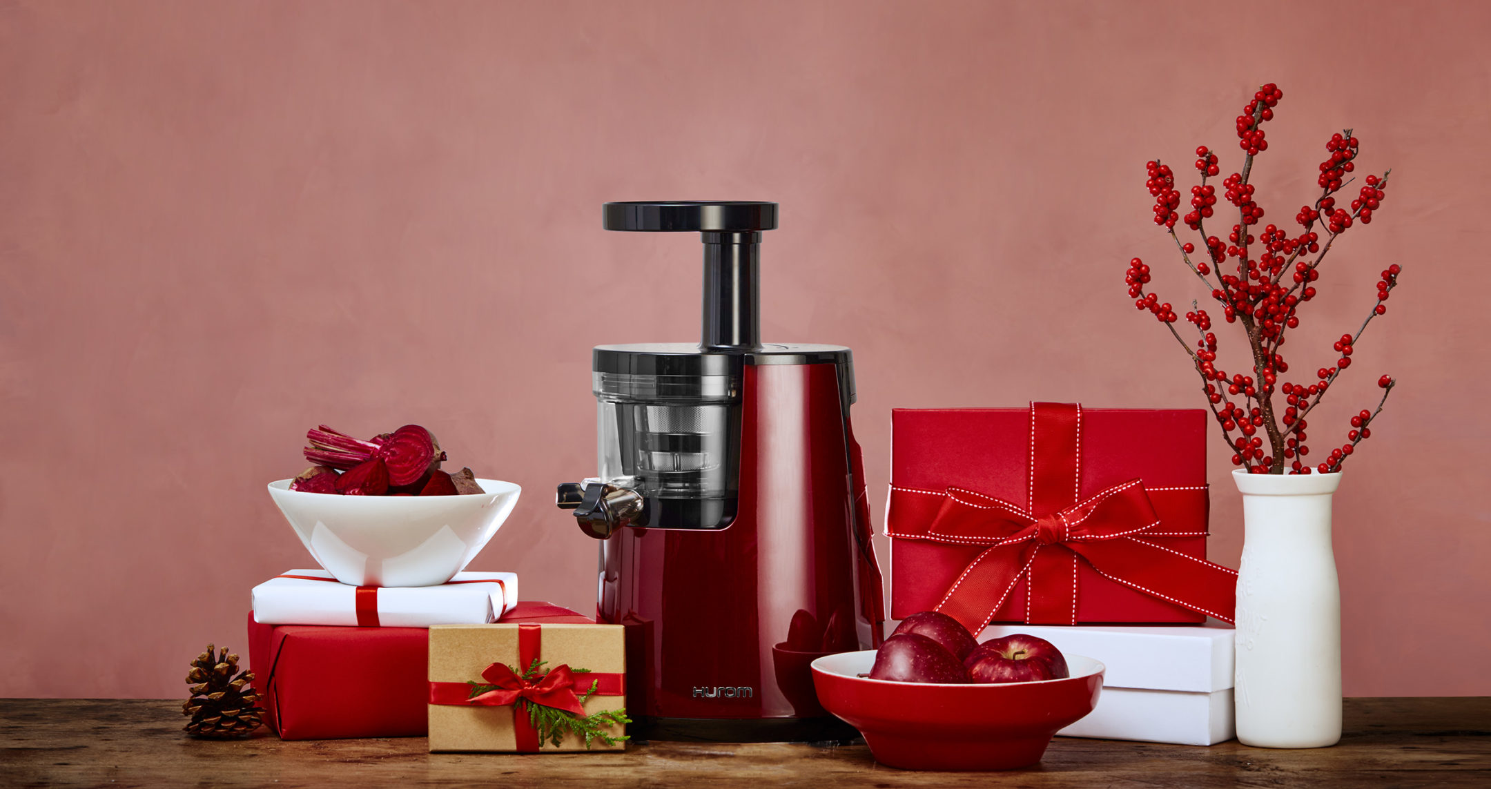 hurom juicer on red background surrounded with gifts