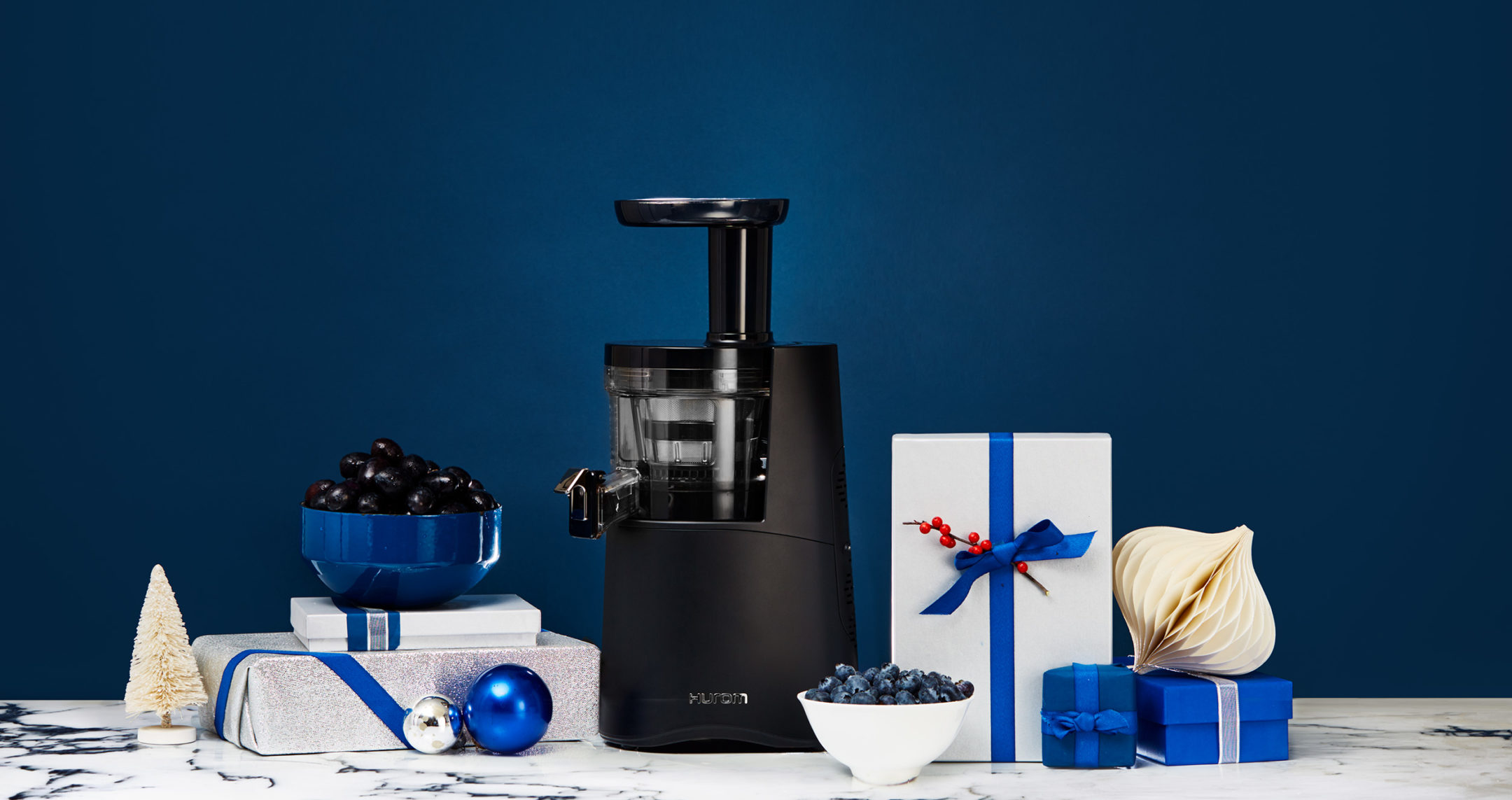 hurom juicer on blue background surrounded by gifts
