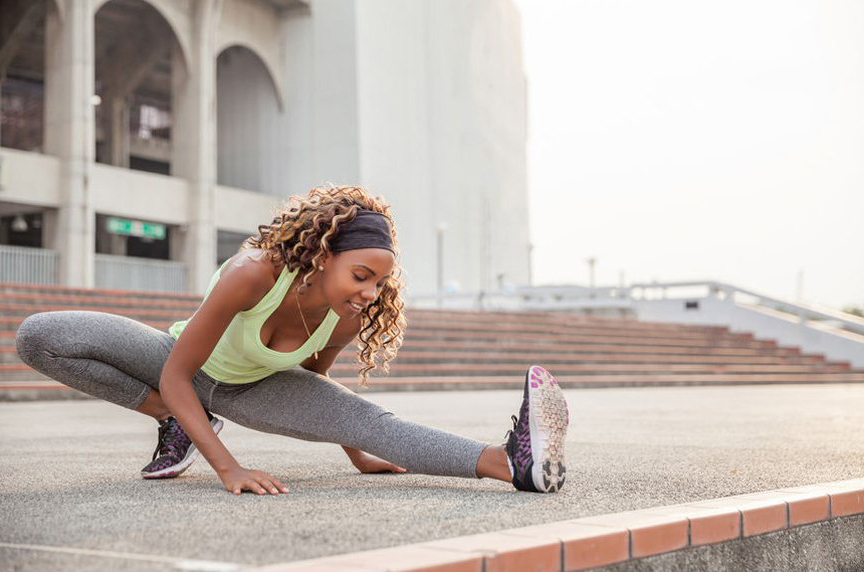 woman stretching outside before a run