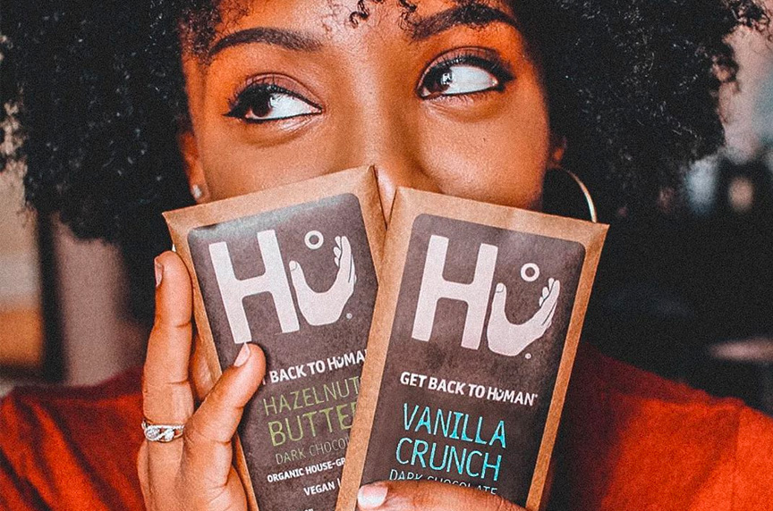 close up of woman holding two hu chocolate bars