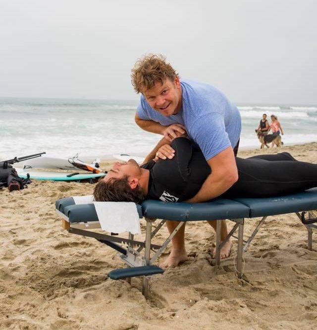 Dr. Glow adjusting a surfer's back