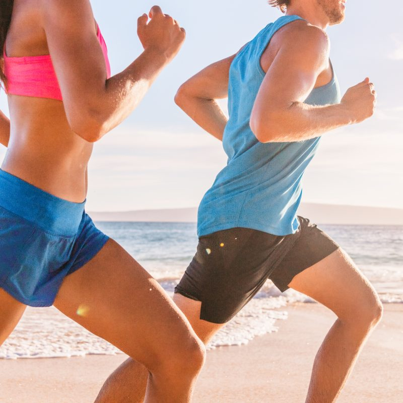 A man and woman running on the beach