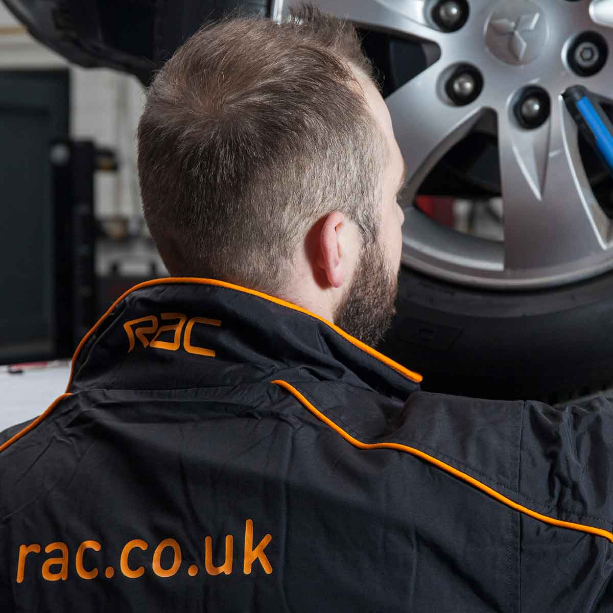A technician wearing RAC overalls attending to a car