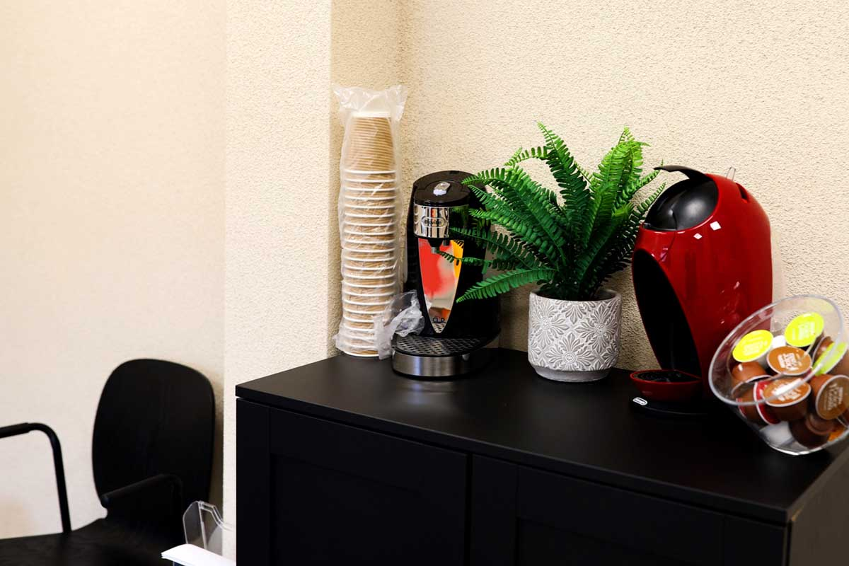 a coffee machine and cups in the reception area
