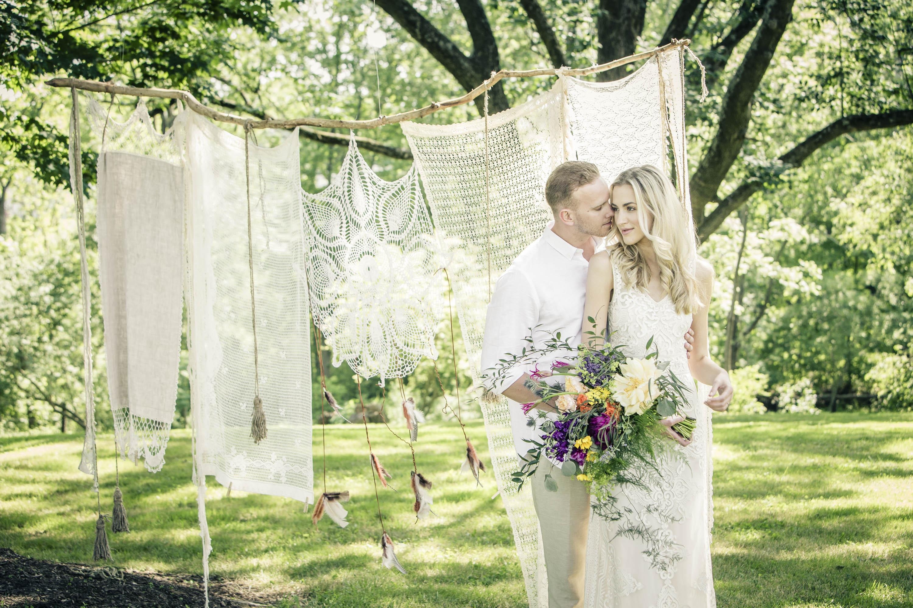 Newlyweds in front of white blankets and feathers hanging from tree