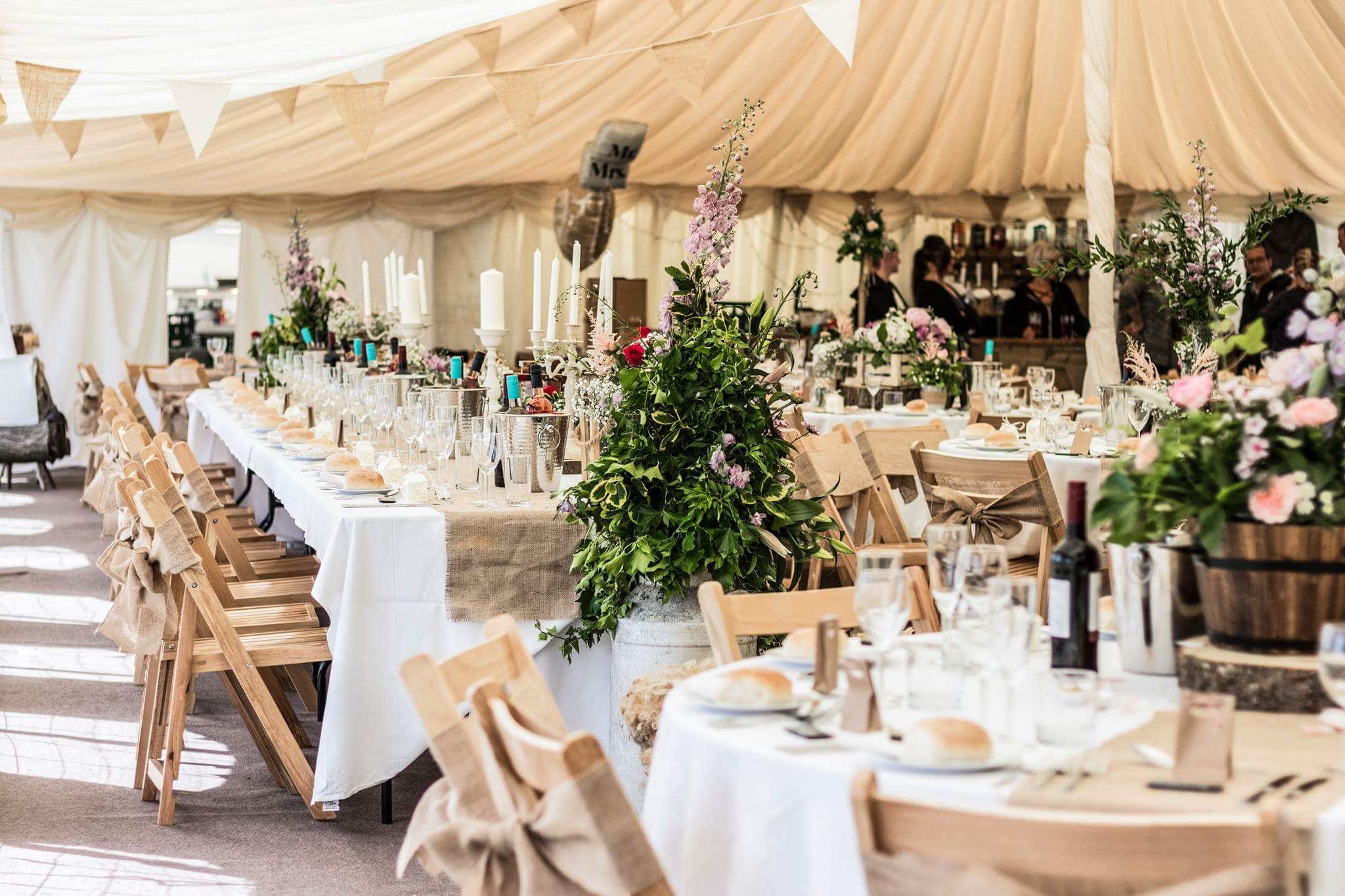 Outdoor wedding under tent decorated in beige, white, and green