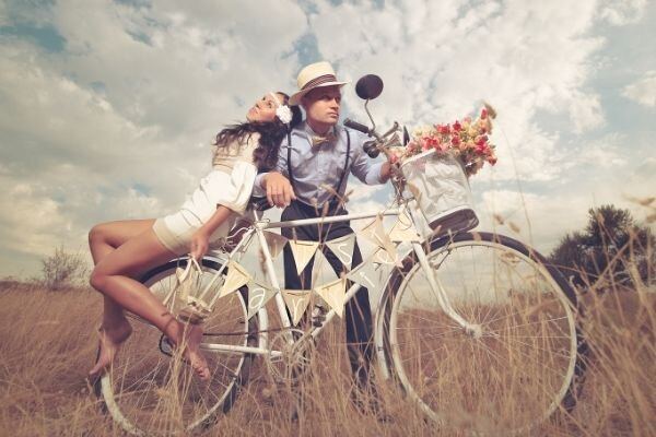 hipster couple leaning on bicycle in grassy field