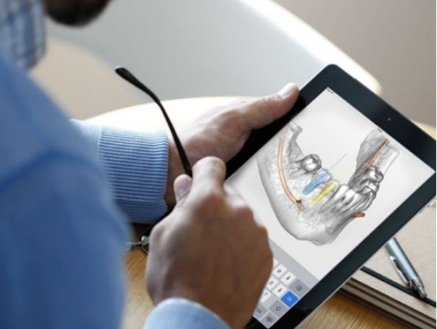 Image of a dentist using software to plan dental implant procedure virtually.