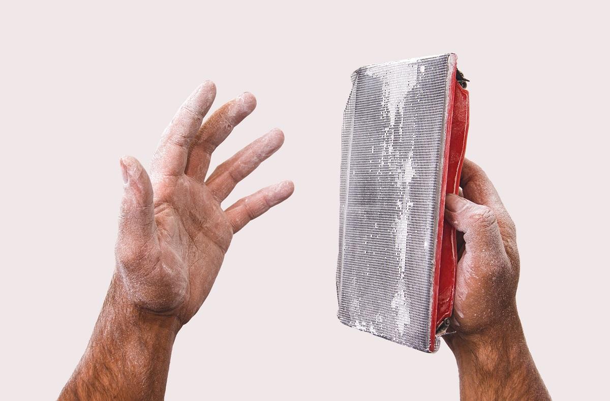 sanding sponge in dusty hands