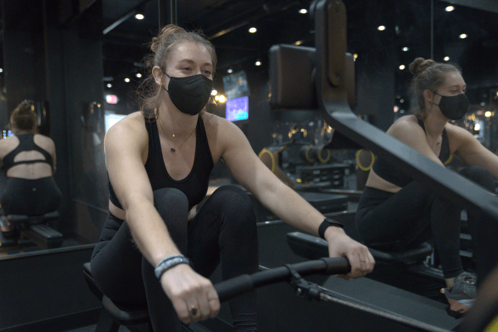 women with a mask on rowing in row republic gym.