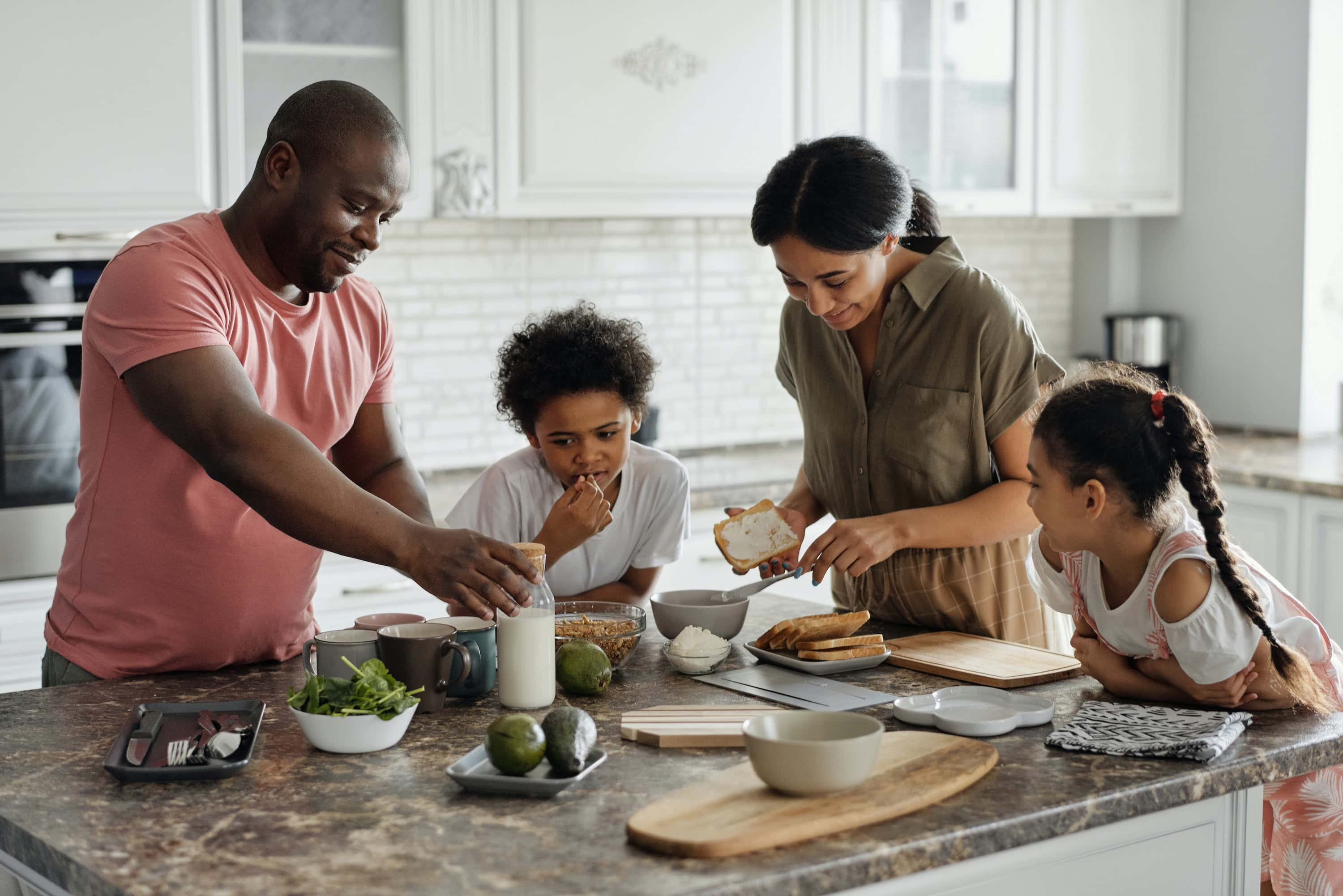 A family gathers at a kitchen island prepping a meal together.