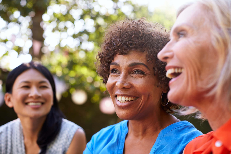 Medium shot of 3 middle aged women smiling.