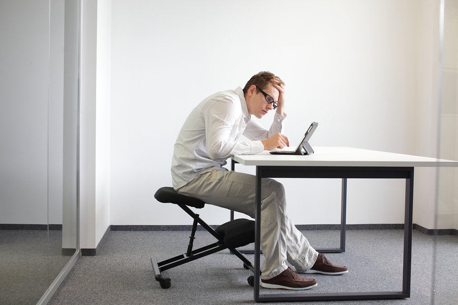 Young man is bent over her tablet in his office,seating on kneel