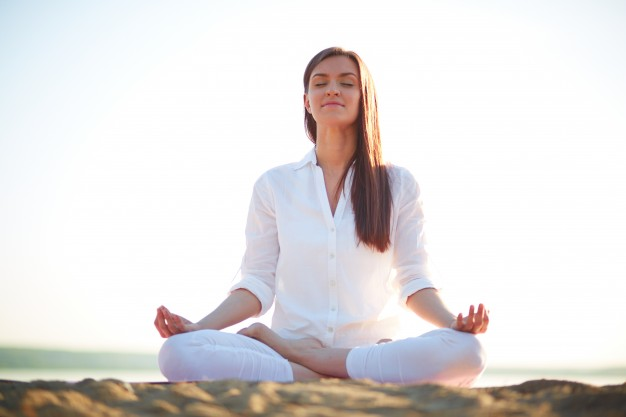 woman-doing-yoga-exercises-on-the-beach_1098-1449