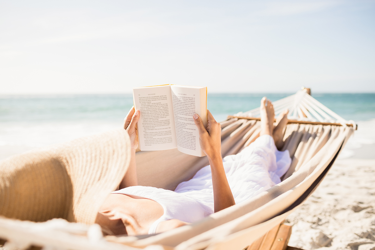 Woman reading book in hammock on the beach|say-no|say-no