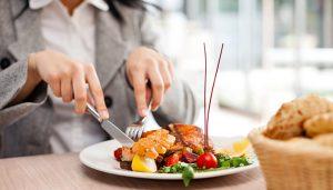 bigstock-woman-eating-at-restaurant-452152301