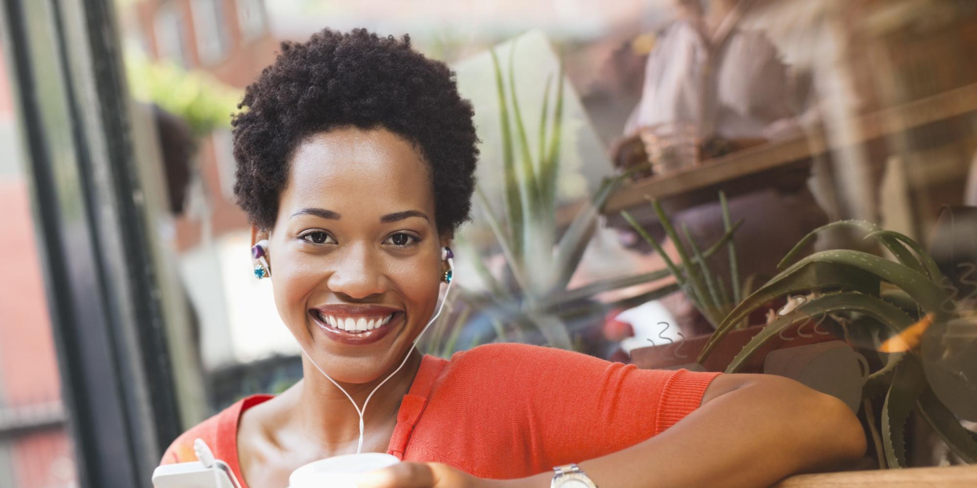 Woman listening to earphones by coffee shop