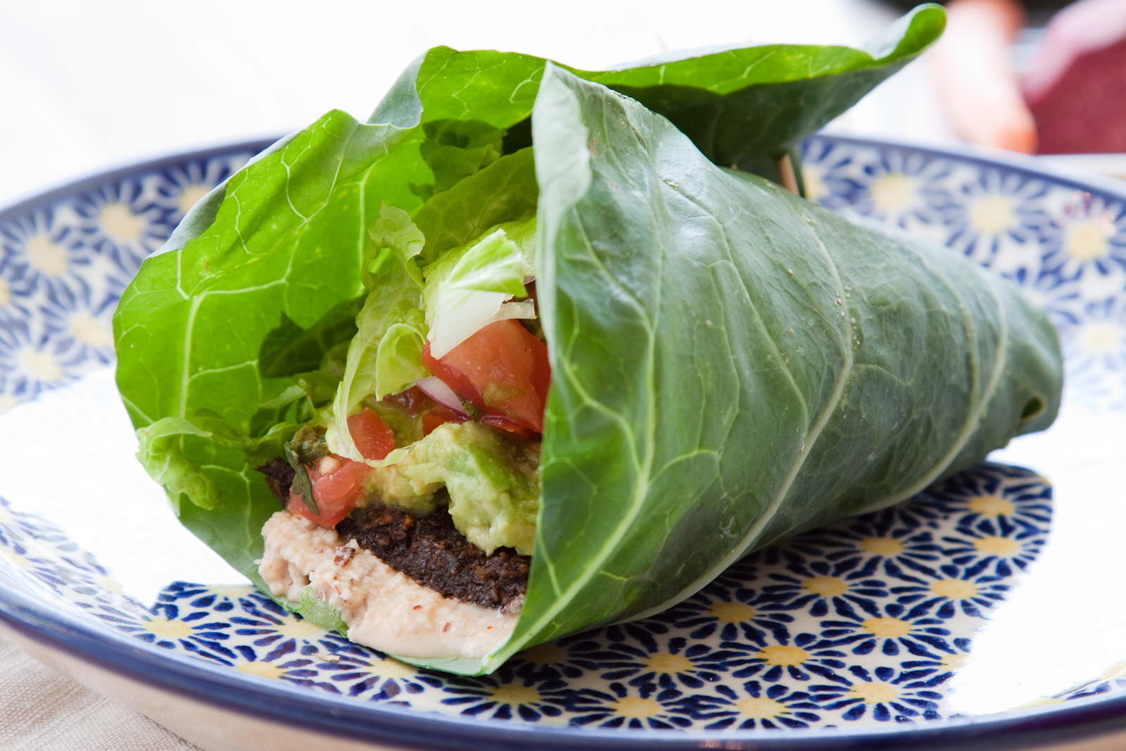 Seasoned nut loaf guacamole romaine lettuce salsa & almond nut cheese wrapped in a collard leaf.