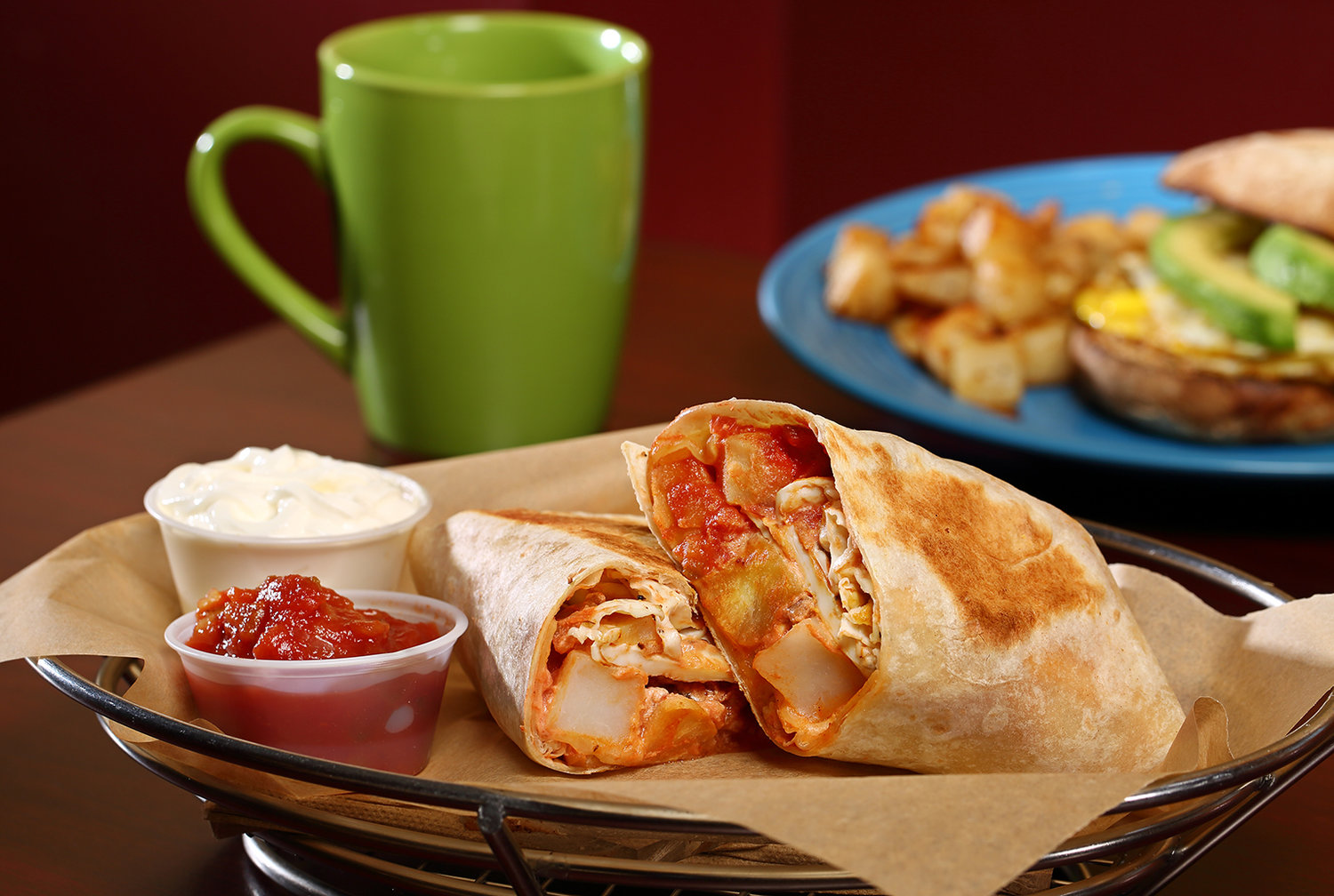 plate of southwest breakfast wrap with a green mug
