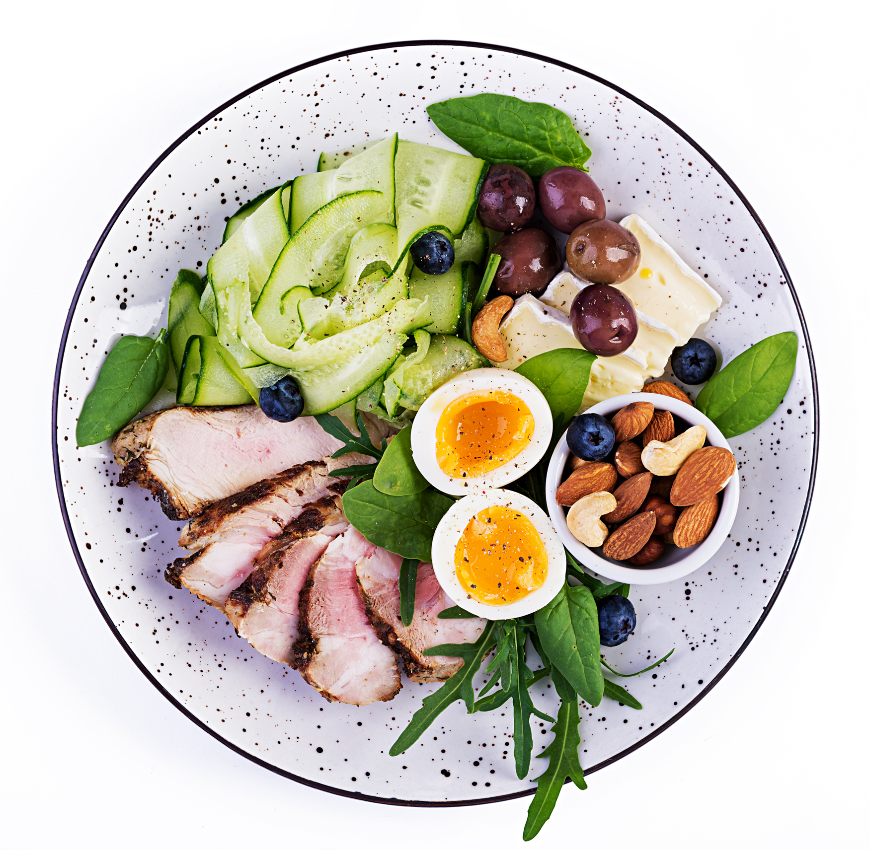 This a large photo of a full meal of vegetables, grapes, nuts, eggs and sliced pork.