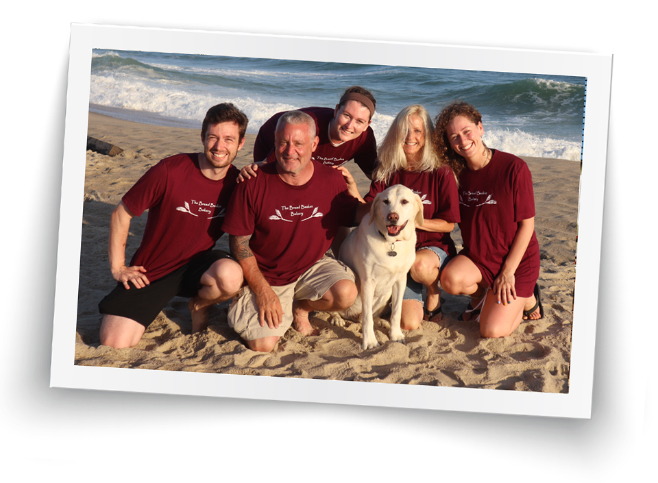 This is a photo of Ed and Lisa Mitzen on the beach with their children and family dog.