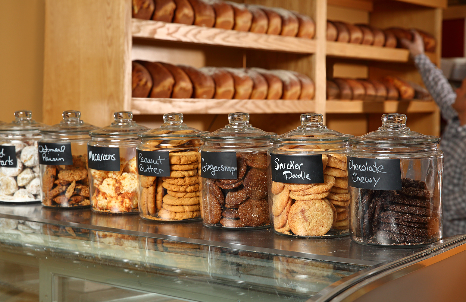 This is a photo from inside the bakery showing a row of glass cookie jars on top of the counter.