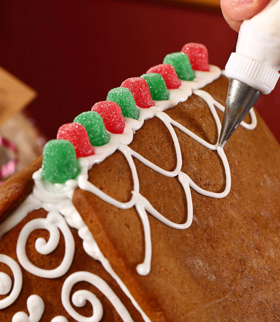 This is a close up photo of a gingerbread house being frosted.
