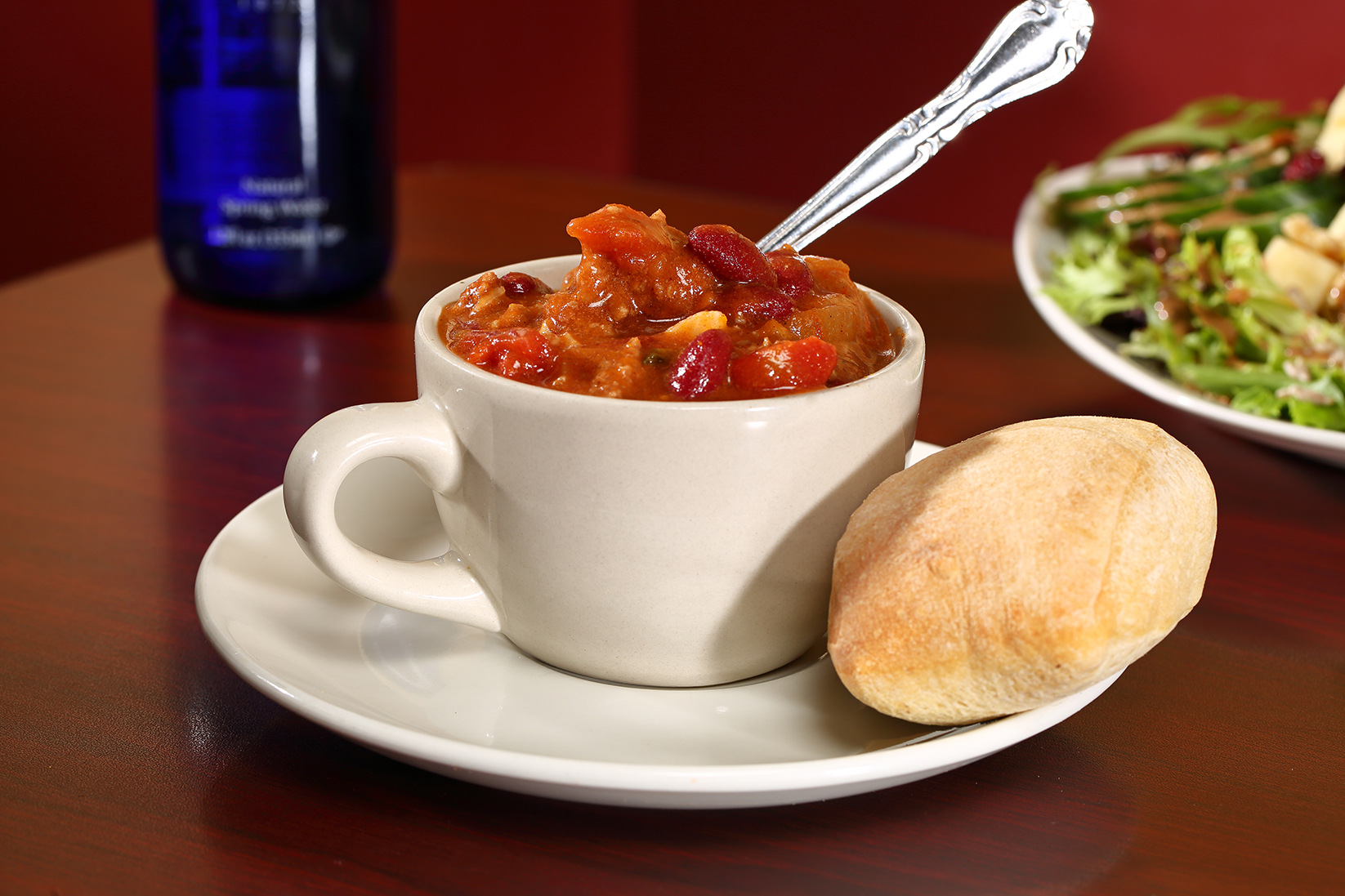 This is a photo of a cup of soup and a small roll on a plate.