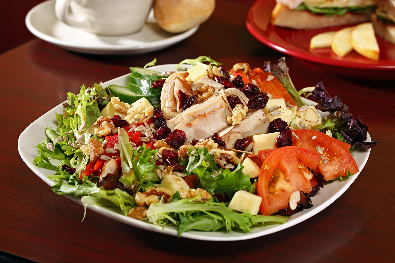 This is a photo of a beautiful salad with greens and tomatoes and raisins, beets and more on a table.