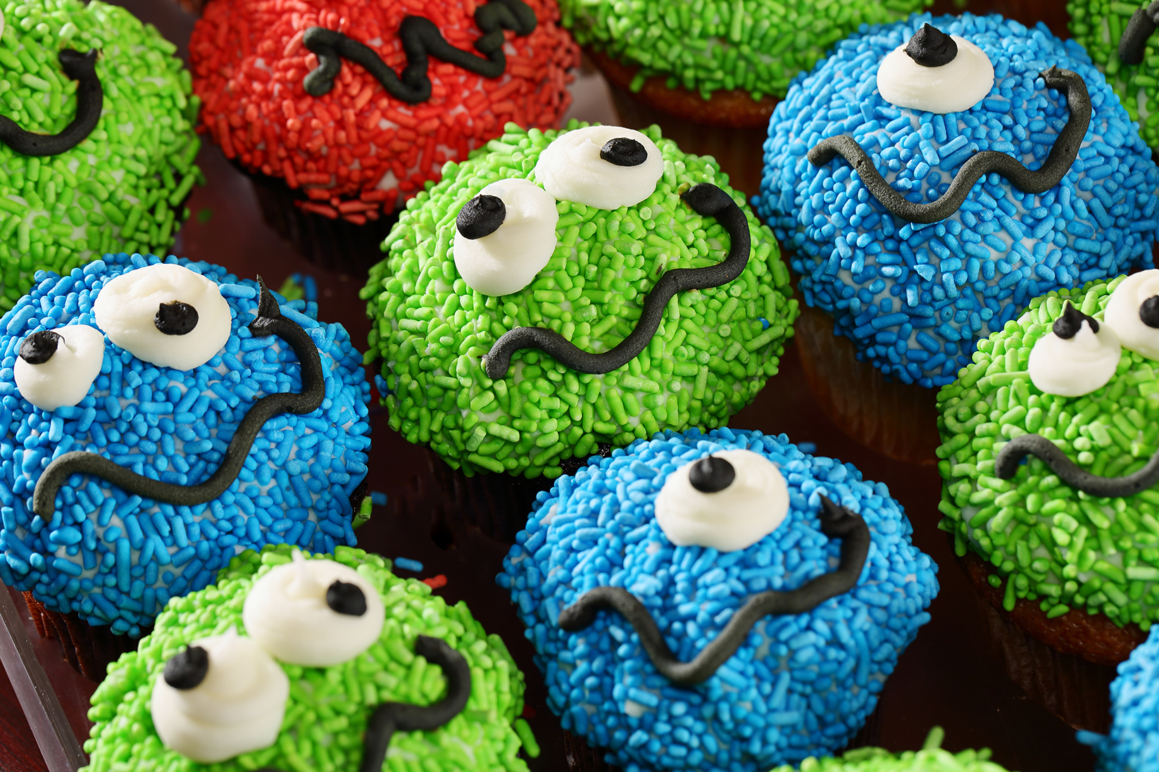 This is a photo of multi color cupcakes covered in sprinkles and smily faces