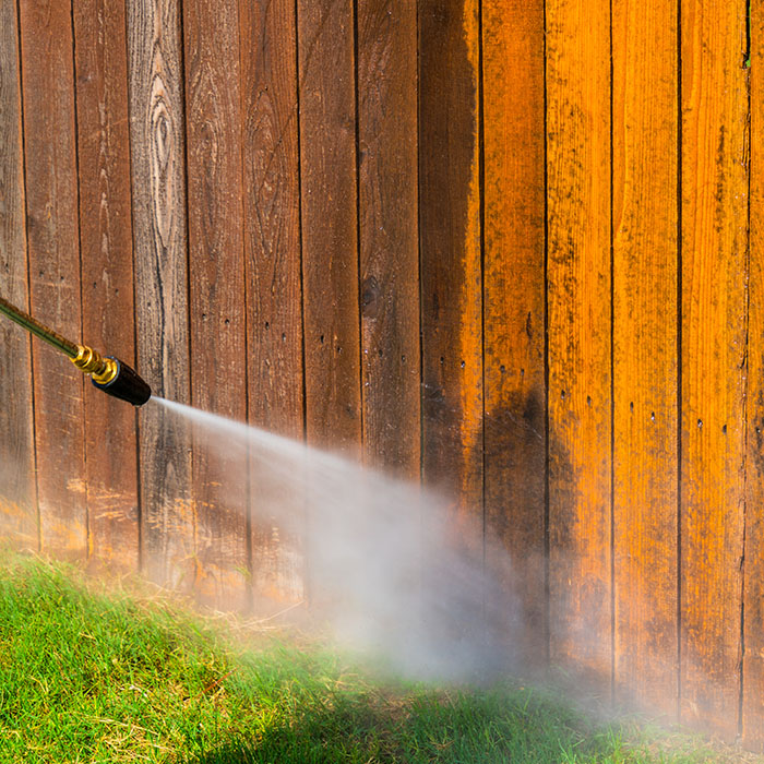 Pressure washing hose spraying wooden fence in Columbus, OH