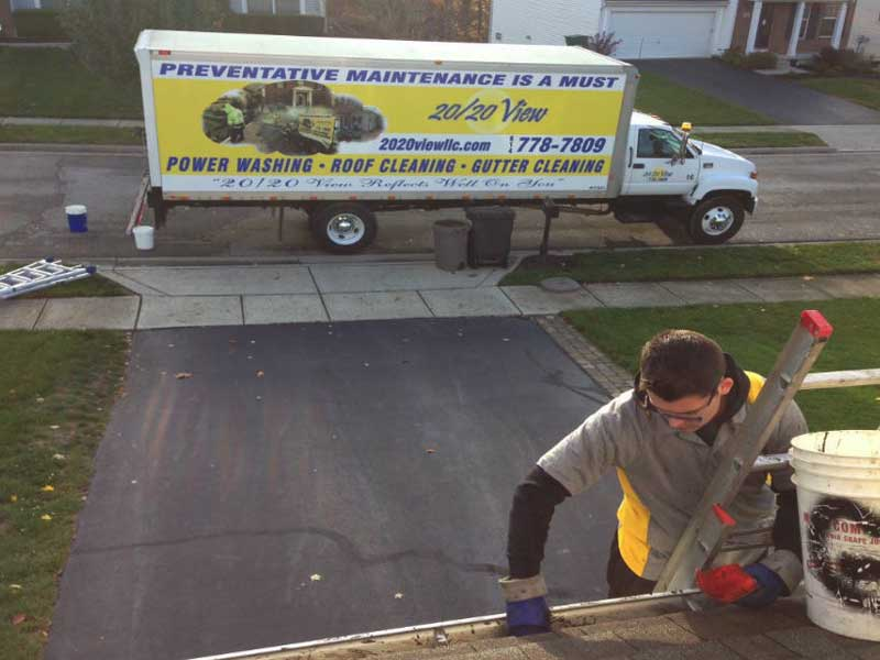 20/20 View employee on ladder cleaning gutters with 20/20 View truck parked on street in Columbus, OH