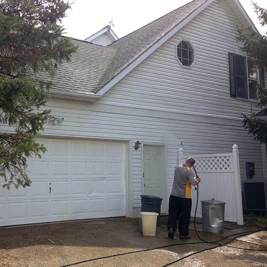 Pressure washing hose spraying house siding in Columbus, OH