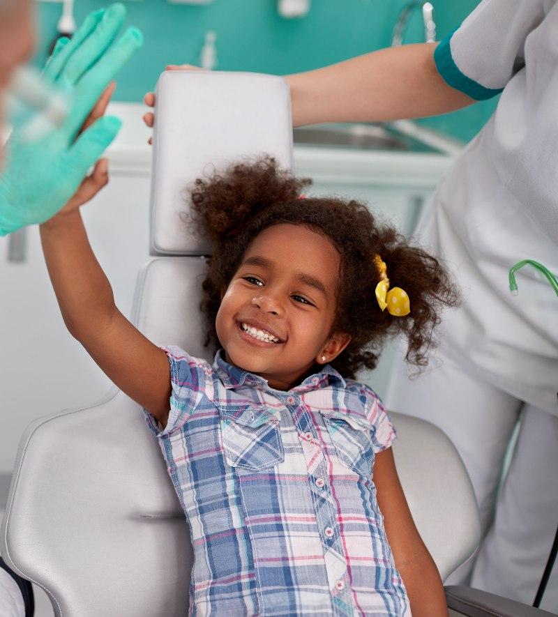 little girl hi-fiving dentist