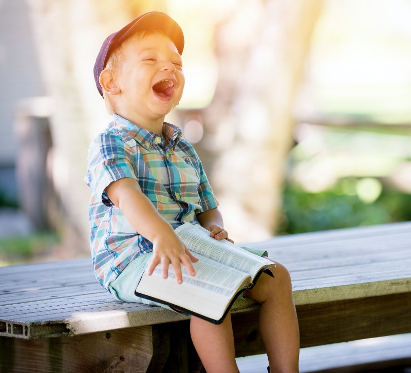 kid smiling with book